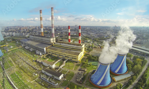 Territory of power plant with many pipes at sunny day
