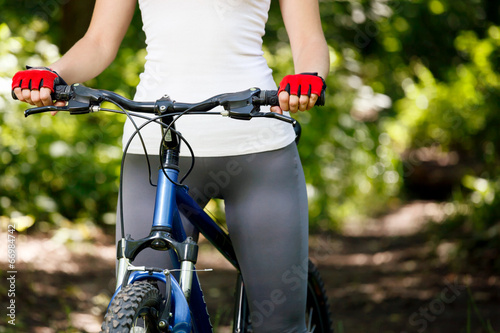 Photo Stands Cycling Closeup of hands in red protective gloves holding handlebar.