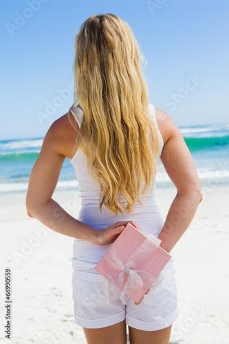 In de dag Bleke violet Blonde hiding present behind back on the beach