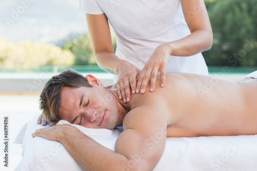 Photo Handsome man getting a massage poolside