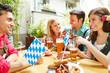 Freunde im Biergarten essen und trinken zusammen