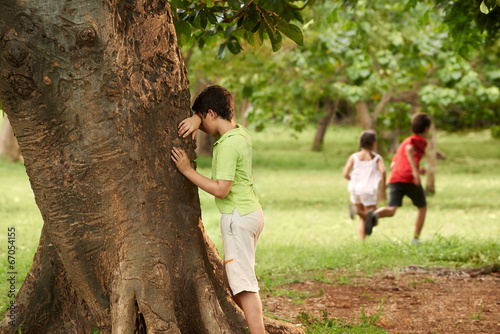 Fotomural male and female children playing hide and seek