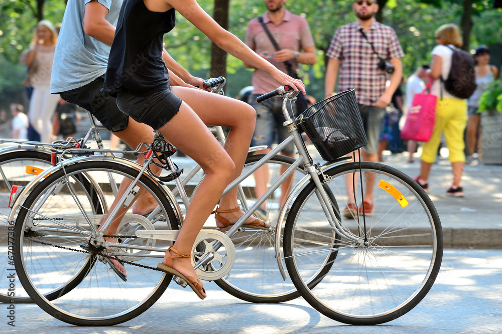 Fototapeta Summer couple on bikes in green city