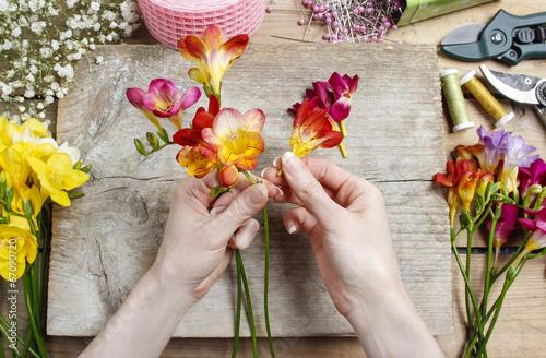 Spoed Foto op Canvas Iris Florist at work. Woman making bouquet of spring freesia flowers