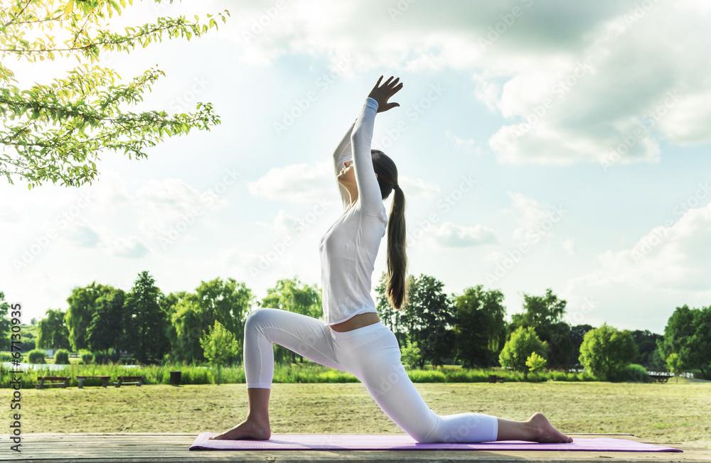 Foto  Hübsche Frau macht Yoga-Übungen im Park.