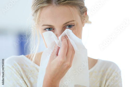 Fotografia, Obraz  Young woman with cold blowing her runny nose