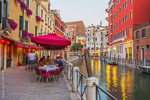 Narrow canal among old colorful brick houses in Venice