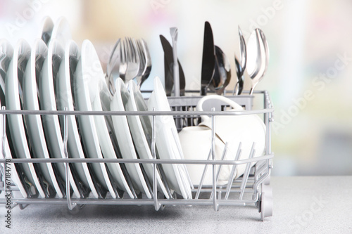 Photo Clean dishes drying on metal dish rack on light background
