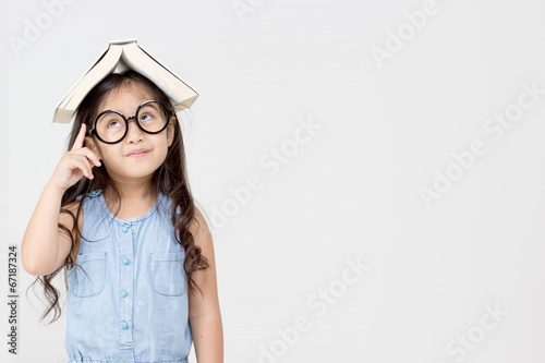 Photo  Portrait of little Asian child thinking and put a book on top
