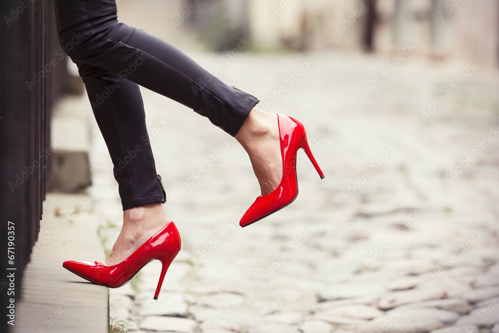 Fototapeta Woman wearing black leather pants and red high heel shoes