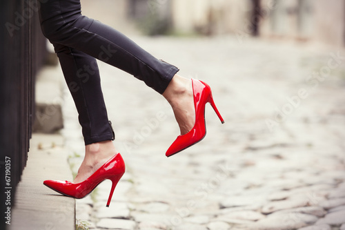 Obraz Woman wearing black leather pants and red high heel shoes - fototapety do salonu