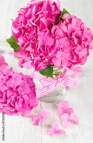 Tuinposter Azalea hydrangea flower in vase on wooden surface