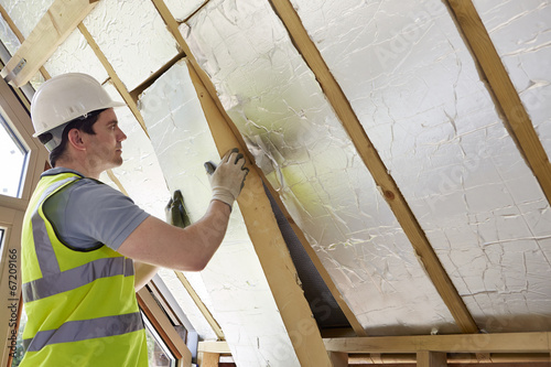 Obraz Builder Fitting Insulation Into Roof Of New Home - fototapety do salonu