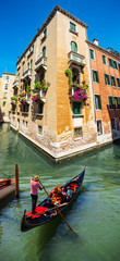 FototapetaNarrow canal among old colorful brick houses in Venice