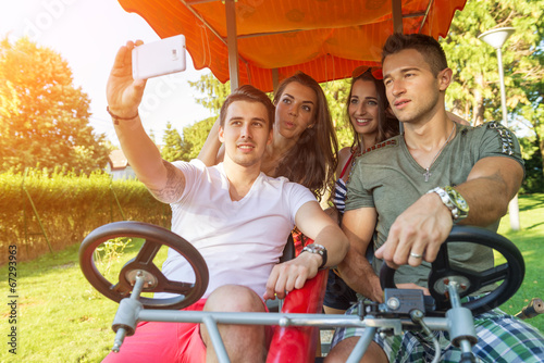 Four young people in a four-wheeled bicycle, they do selfie