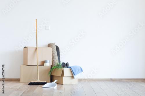 Fotografie, Obraz  Umzugskartons mit Schaufel und Besen vor einer weißen Wand