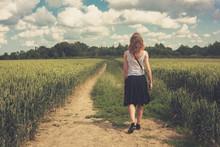 Young Woman Walking In A Wheat Field