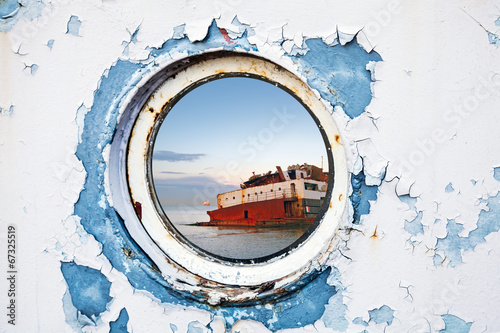 Foto op Canvas Schipbreuk Ship wreck behind round porthole in white and blue wall
