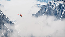 Red Airplane Flying Over Snow ...