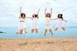Four girlfriends jumping on beach