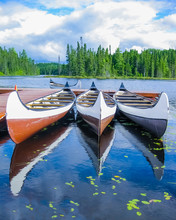 Canoes Reflected On A Turquois...