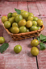 Yellow plums in a basket on wooden background
