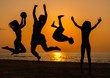 Silhouettes a young people having fun on a beach against sunset