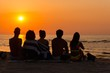 canvas print picture - Silhouettes a young people sitting on a beach looking at  sunset