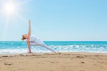 Caucasian Woman Practicing Yoga On The Beach