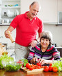 Loving elderly couple cooking with tomatoes