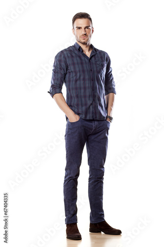 Fototapeta young man posing with his hands in pockets obraz