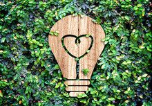 Light Bulb Wood Icon And Heart Shape Inside On Green Leaf Wall,E