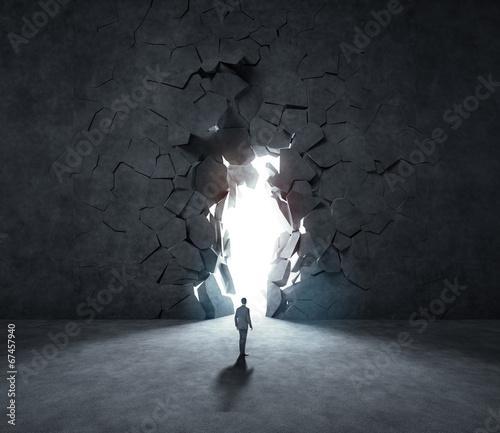 Fotografering  businessman breaking trough a wall