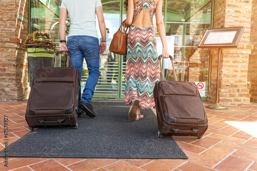 Young couple standing at hotel corridor upon arrival Wallpaper Mural