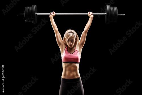 Muscular woman lifting a he...