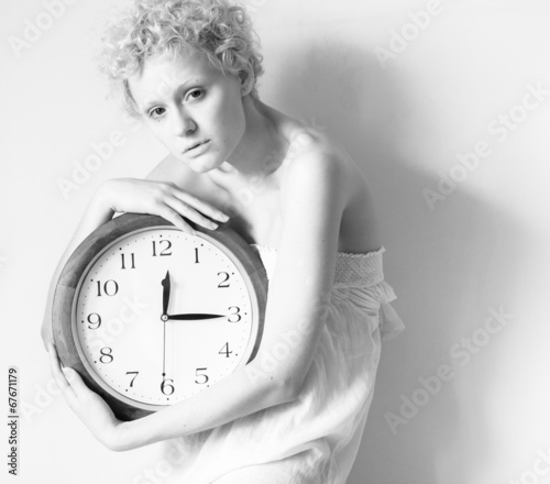 Fotografija  Conceptual portrait of woman in bed with big clock.