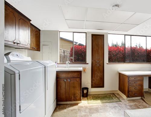 Fototapeta Bright laundry room with dark brown cabinets obraz na płótnie