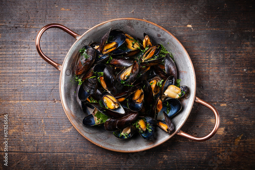 Valokuva  Boiled mussels in copper cooking dish on dark wooden background