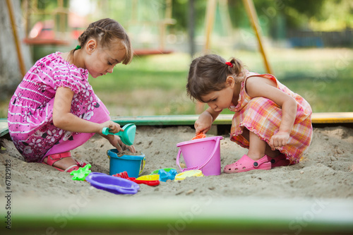 Photo  Two girls play in the sandbox