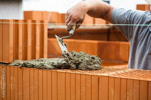 Fotografia, Obraz  Maurer mit Ziegelmauer auf Baustelle