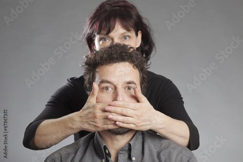 Frau hält Mann den Mund zu. - kaufen Sie dieses Foto und