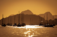 Boats On Water By Sunrise With Mountans In The Horizon