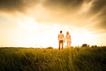 Couple Walking Through The Fie...