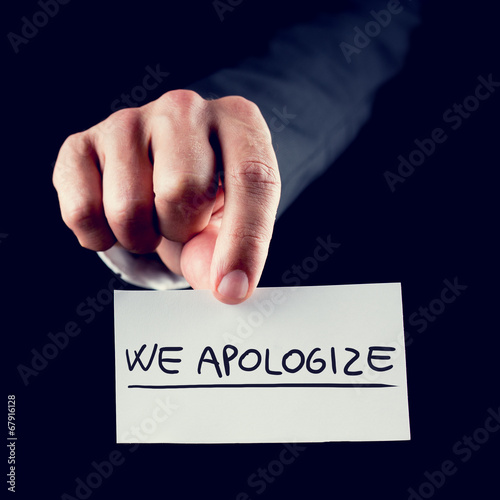 Photo Businessman holding a card reading We Apologise