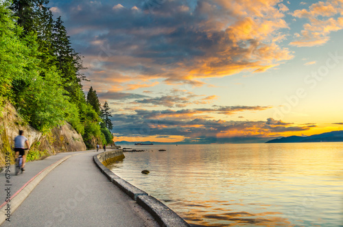 Fotografía  Sunset over The Seawall of Vancouver with cyclist in motion