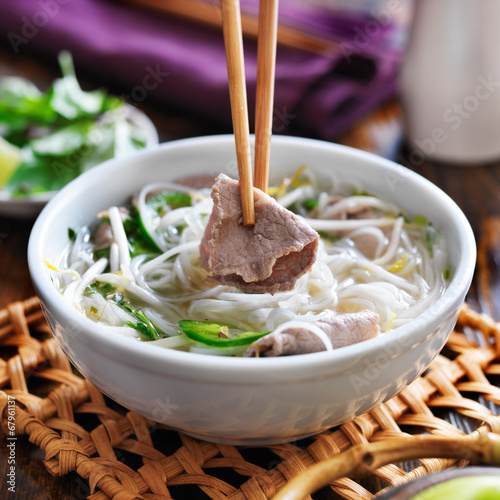 eating a bowl of pho with chopsticks and picking up beef Canvas Print