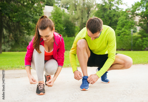 Fotografía  smiling couple tying shoelaces outdoors