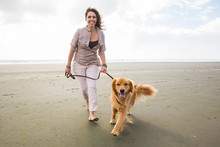 Adult Woman Walking A Golden R...