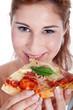 Junge Frau isst Pizza und lächelt