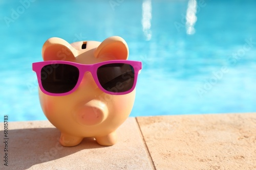 Fotografía  Summer piggy bank with sunglasses in front of a swimming pool